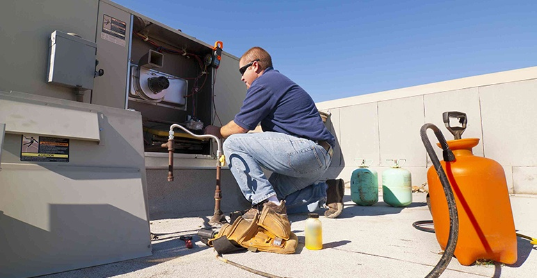 HVAC technician inspecting HVAC unit that might need to be replaced
